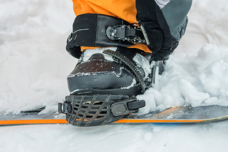 black boots: The man in black boots buttons fastening snowboard.
