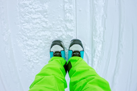 freeride: Top view of a foot in the snowboard boots and bright pants.