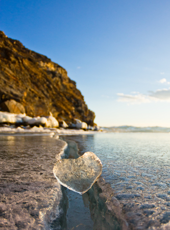 Icy heart in a crack in the light of sunset. lake Baikal.