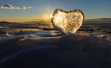 Icy heart in the waves in the light of sunset. lake Baikal.