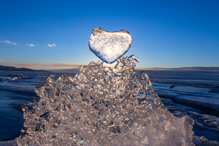 Sun at sunset shines through the icy heart on texture transparent ice floe in Lake Baikal.