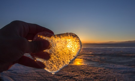 Icy heart in his hand in light of sunset. lake Baikal. Stock Photo