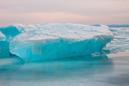 Arctic blue glacier ice hummock in cloudy weather. Stock Photo
