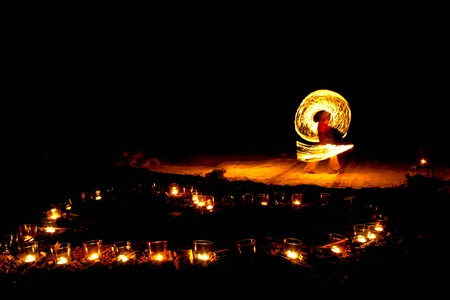 Heart shape of burning candles on the ground on a background of fire show.