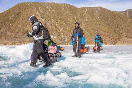 Lake Baikal, Russia - March 24, 2016: The men dragged the ice sledge through a crack in the ice of Lake Baikal in the March 24, 2016