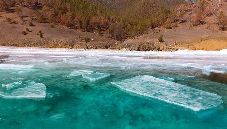 Growers ice iceberg in turquoise water of Lake Baikal.