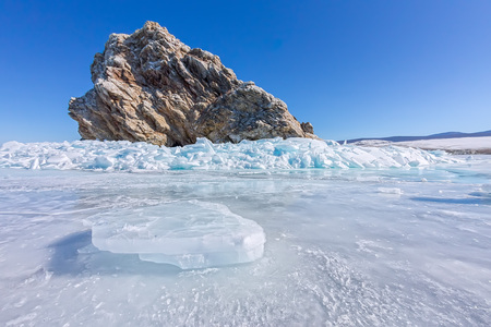 baical: Rock Yador on Olkhon Island in winter, surrounded by the blue ice of Lake Baikal with cracks