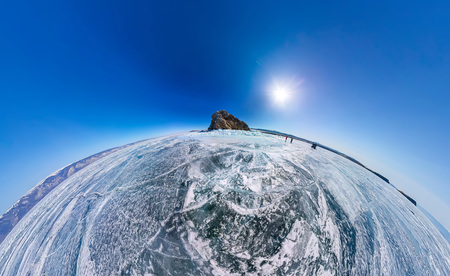 Aerial panorama Shaman Rock or Cape Burhan on Olkhon Island in winter, surrounded by the blue ice of Lake Baikal with cracks.