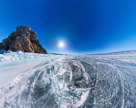 baical: Aerial panorama Shaman Rock or Cape Burhan on Olkhon Island in winter, surrounded by the blue ice of Lake Baikal with cracks.
