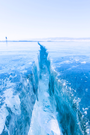 Wide crack in the ice of Lake Baikal. Stock Photo