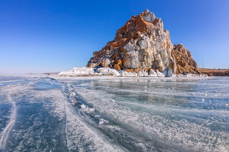 baical: Shaman Rock or Cape Burhan on Olkhon Island in winter, surrounded by the blue ice of Lake Baikal with cracks Stock Photo