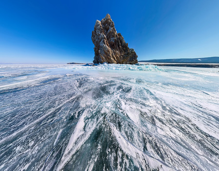equirectangular: Aerial panorama Shaman Rock or Cape Burhan on Olkhon Island in winter, surrounded by the blue ice of Lake Baikal with cracks.