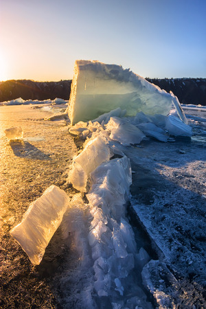 Ice hummock at the crack in the winter Baikal at sunset.