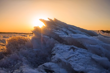 Melted snow icy wave in the light of the setting sun. Stock Photo