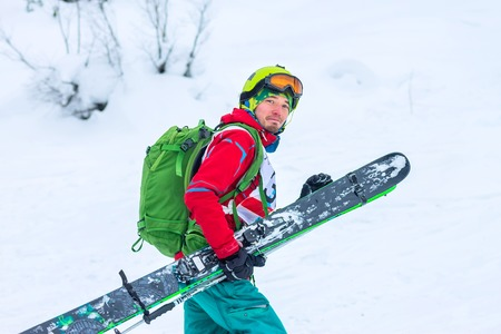 Freerider skier with skis in hand is smiling, portrait, isolate,