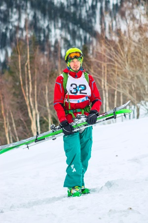 Freerider skier with skis in hand is smiling, portrait, isolate.