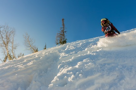 Freerider girl snowboarder slides from the mountain in the light of the sun.
