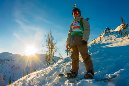 BACKFLIP: Freeride snowboarder stands on hillside in light dawn sun. Stock Photo