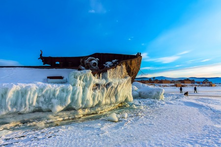 Old rusty ship on ice covered sunset standing on the shore. Stock Photo