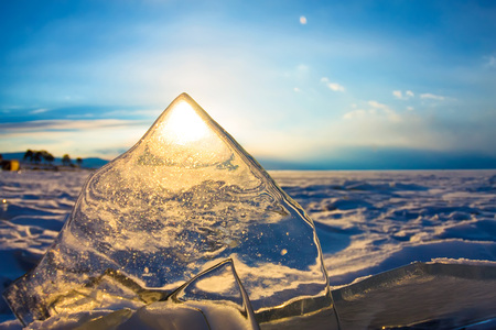 Sun at sunset shining through the transparent texture of the ice.