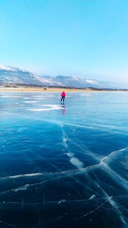 Skater girl on the ice of Lake Baikal Olkhon.
