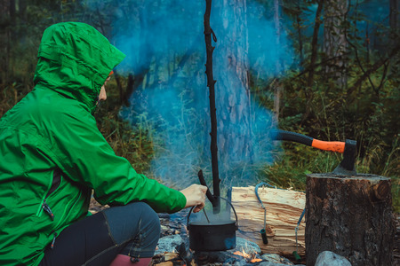 survive: Woman traveler cooking food in kettle on fire in forest Stock Photo