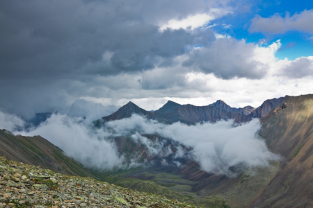 shamanism: Peaks of rocky mountains in clouds and fog. Stock Photo