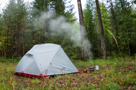 Tent in the wood and the water is boiling in the pot at the gas burner.