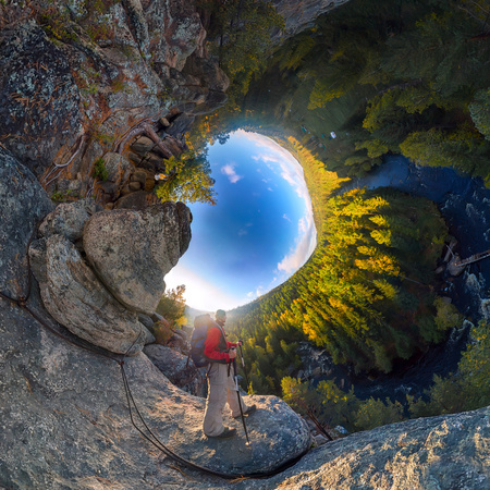 Backpacker on top of a rock fall at dawn. spherical degree panorama 360 180 little planet. Foto de archivo