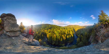 Backpacker on top of a rock fall at dawn. Spherical panorama 360 180 degrees equidistant.