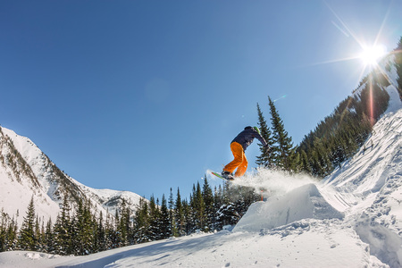 Snowboarder freerider jumping from a snow ramp in the sun on a background of forest and mountains. 版權商用圖片 - 87676372