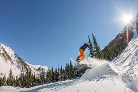 Snowboarder freerider springen van een sneeuwhelling in de zon op een achtergrond van bos en bergen.