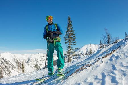Man skier freerider standing at top of ridge, adventure winter freeride extreme sport. Stock Photo