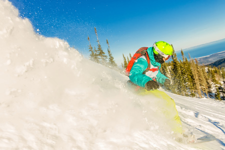 Freeride snowboarder slides down a steep slope at dawn.