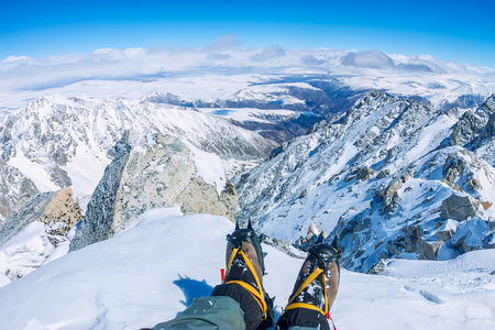 crampon: First person view to legs in crampons take a rest on the top of mountain.