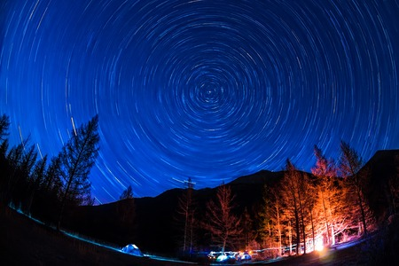 Star Trail in sky above the mountains fire in the tent camp. Stock Photo