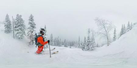 Man skier freerider standing at top of ridge, adventure winter freeride extreme sport. Фото со стока