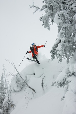 Skier freerider jumping from a snow ramp in the sun on a background of forest and mountains.