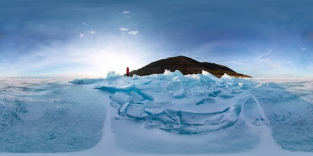 Woman in blue hummocks of the ice Baikal at sunset. Imagens