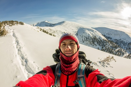 A male traveler taking a selfie with a backpack in the winter mountains.