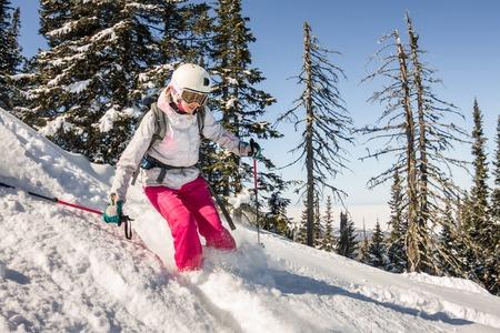 A female skier rides through powder snow to the mountains during winter sport