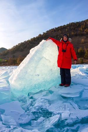 girl stands among the large blue ice ridges of Lake Baikal. Фото со стока