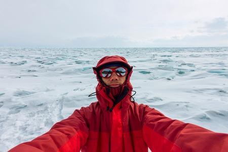 Selfie portrait of a man in a snowy Baikal in hummocks.