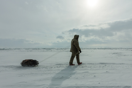 Woman with a sledge walk is on the ice of Lake Baikal.