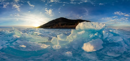 A blue hummocks shaped ice Baikal at sunset.