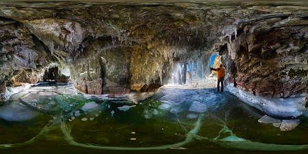 Panorama man in an ice cave with icicles on Baikal, Olkhon, Spherical 360 vr degree panorama. Stock Photo
