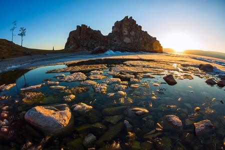 Melting spring ice of Lake Baikal, on the rock Shamanka at sunset.