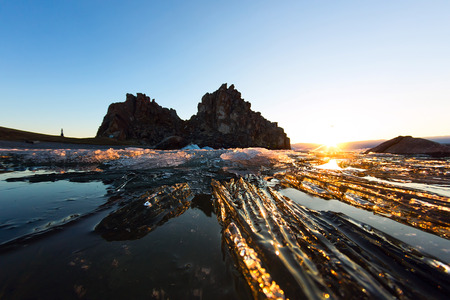 Melting spring ice of Lake Baikal, on the rock Shamanka at sunset.
