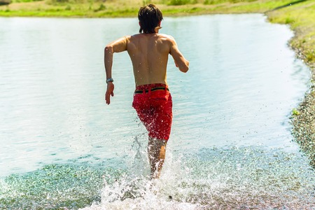young korean man runs his back on the water with a smile and a naked torso.