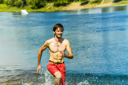 Korean young man running on water with a smile and a naked torso.